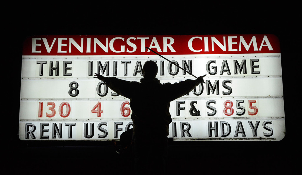 Justin Day changes a movie title on the marquee at the Eveningstar Cinema in Brunswick.