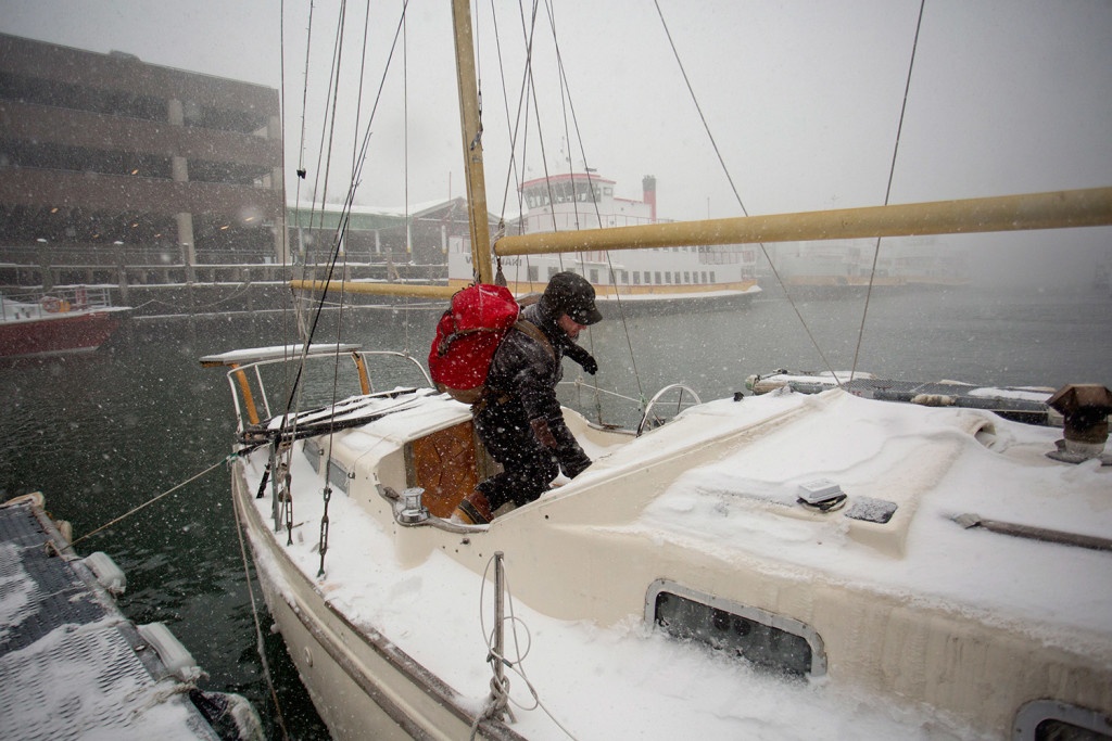 JAN. 27: Jack Marrie enters his 30-foot fiberglass ketch Rime, where he lives year-round, during the Tuesday blizzard. Marrie said he did nothing special to prepare for the storm, and that winter can actually be easier than summer when it comes to living on a boat.