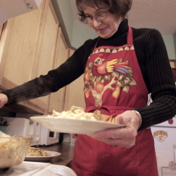 Bonnie McKenney dishes up homemade tuna noodle casserole in her Boothbay Harbor kitchen. Her recipe uses only ingredients she gets at the food pantry or with food vouchers.