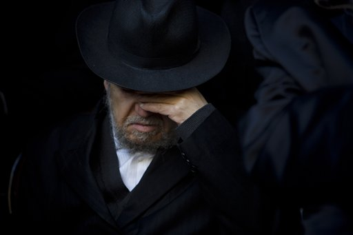 A relative of French Jew Yoav Hattab, a victim of the attack on kosher grocery store in Paris, attends his funeral procession in the city of Bnei Brak near Tel Aviv Tuesday. The Associated Press
