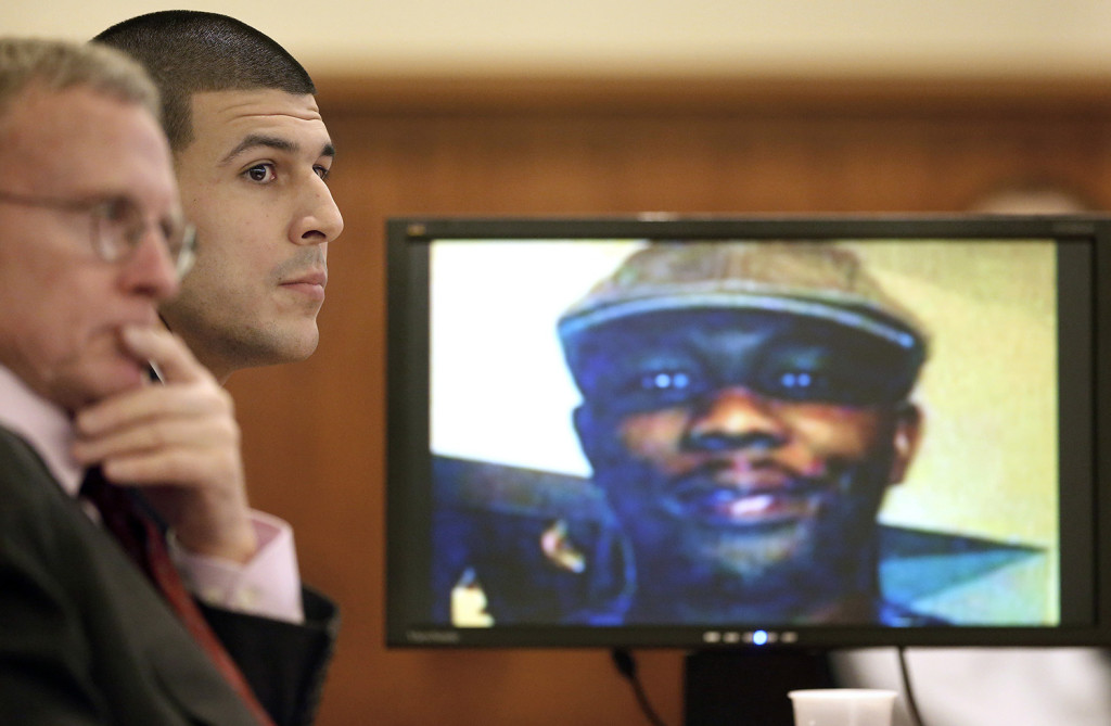 Former New England Patriots football player Aaron Hernandez, center, listens during his murder trial Thursday,in Fall River, Mass., while an image of Odin Lloyd is displayed on a monitor. Hernandez is charged with killing Lloyd, 27, a semiprofessional football player, in June 2013. The Associated Press