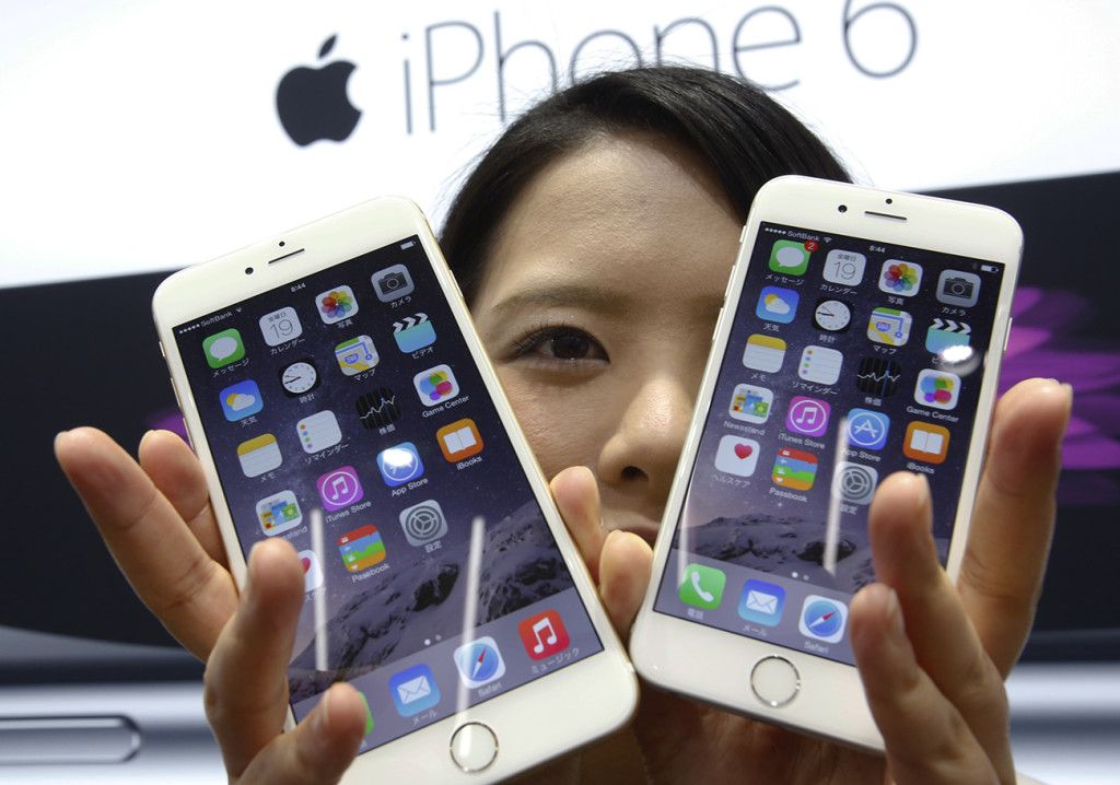 A customer shows off the new Apple iPhone 6 and 6 Plus at a store in Tokyo in this Sept. 19, 2014,  photo. Overall, Apple reported $74.6 billion in sales and $18 billion in profits for the December quarter, a year-over-year increase of 30 percent and 38 percent respectively. The Associated Press