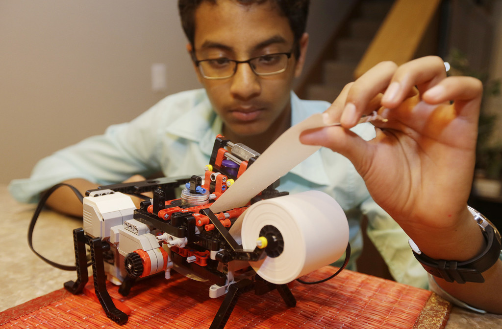 Shubham Banerjee  works on his Lego robotics Braille printer prototype at home in Santa Clara, Calif. He aims to develop a low-cost printer based on the prototype. Last month, tech giant Intel Corp. invested in his startup, Braigo Labs. The Associated Press