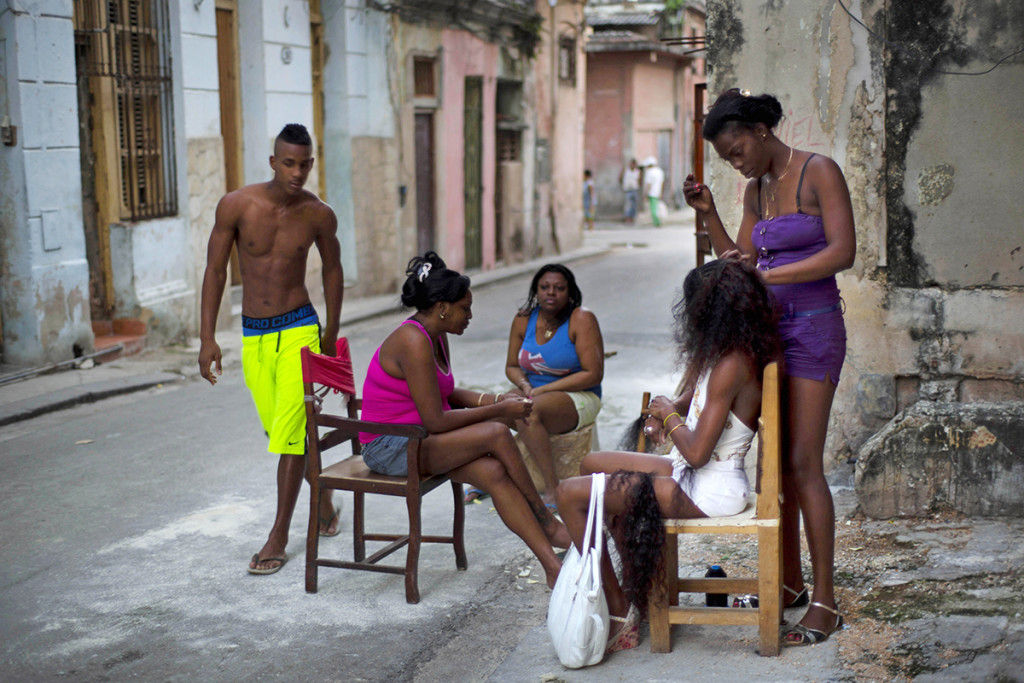Hairdresser Lisandra works on a woman's extensions as others wait their turn in Old Havana, Cuba, on Tuesday. Lisandra attends her clients on the sidewalk outside her home. The Associated Press