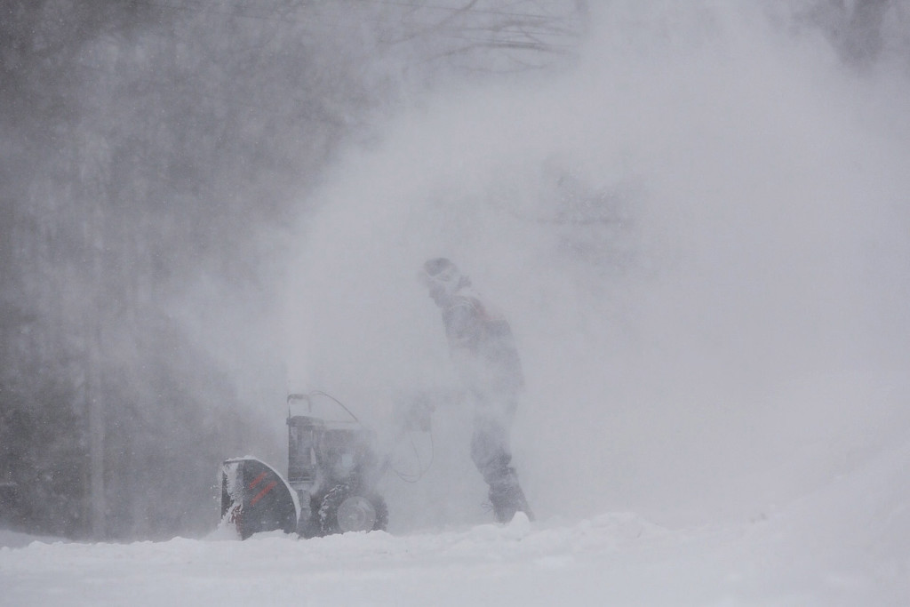 A Scarborough man uses his snowblower to clear his driveway Tuesday during the storm.