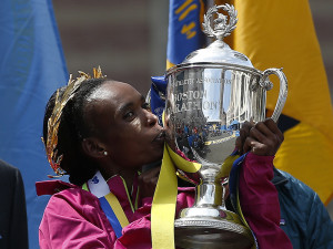 Rita Jeptoo, of Kenya, kisses the trophy after winning the women's division of the 118th Boston Marathon in 2014.
