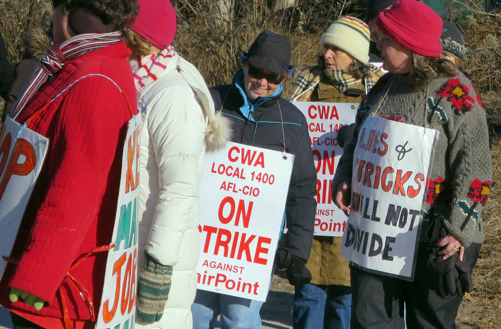 Striking FairPoint Communications workers walk a picket line outside the company's Maine headquarters in Portland last month.