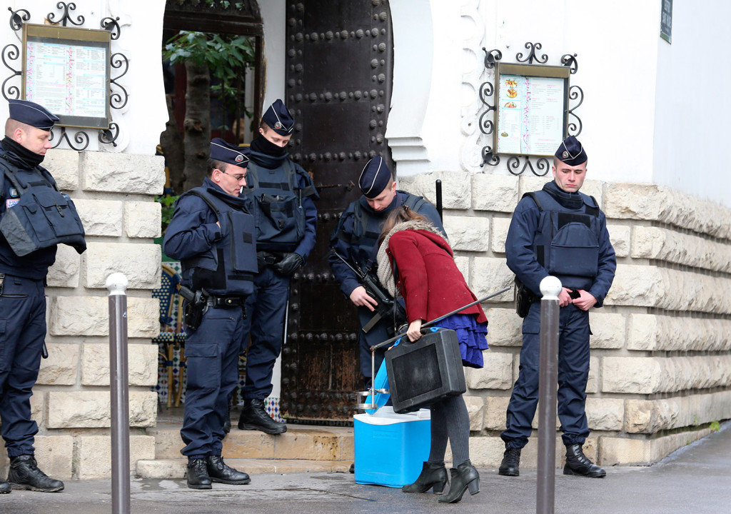 Riot police officers check a woman at the Grand Mosque of Paris, France, on Wednesday, one week after the attack on a satirical newspaper.