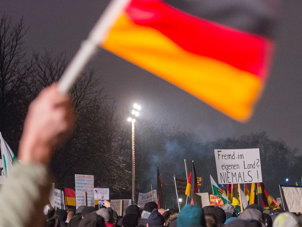 "A participant of a rally by Patriotic Europeans against the Islamization of the West waves a German flag during a demonstration in Dresden, Germany, on Monday. The words on the banner, right, read: ""Foreign in our own country? Never."" Over the last three months, the crowds at PEGIDA's demonstrations in the eastern city of Dresden, a region that has few immigrants or Muslims, have swelled from a few hundred to 17,500 just before Christmas."