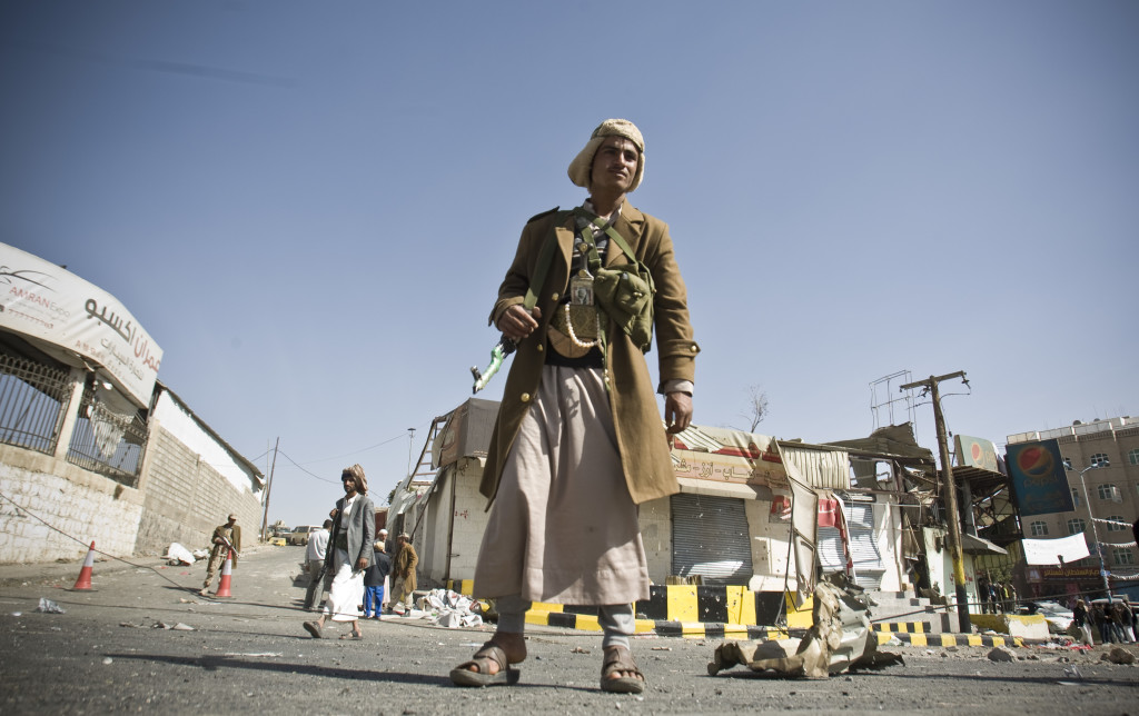 A Houthi Shiite Yemeni stands guard in front of a building damaged during clashes near the presidential palace in Sanaa, Yemen, Tuesday. The Associated Press