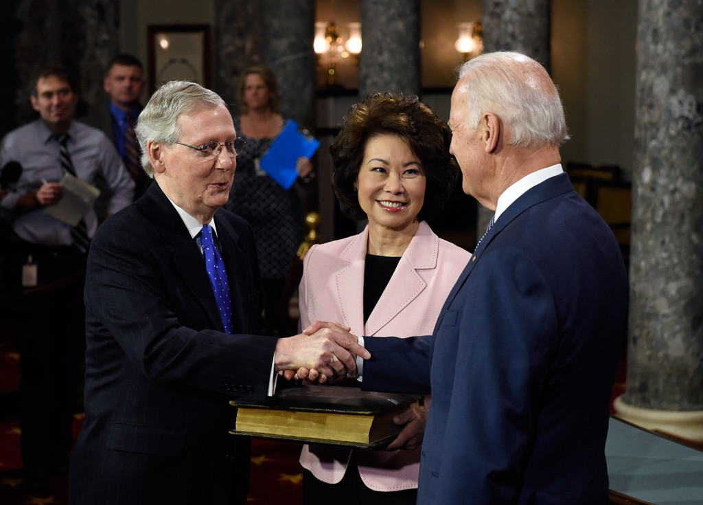 Vice President Joe Biden shakes hands with Senate Majority Leader Mitch McConnell of Kentucky after Biden administered the Senate oath during a re-enacted swearing-in ceremony Tuesday in Washington. McConnell's wife, former Labor Secretary Elaine Chao, is at center.