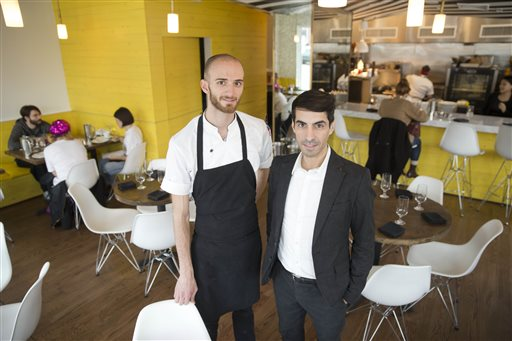 Co-owner Cristian Mora, right, and Chef Brian Oliveira at Girard Brasserie and Bruncherie, where  servers earn about $13 an hour. They also get sick time, vacation days and health insurance. The Associated Press