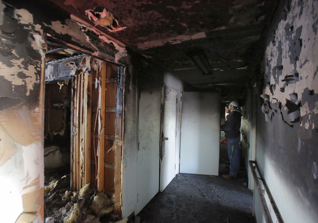 Workers look over damage done by a fire in an apartment complex at 6 School Street in Old Orchard Beach on Thursday morning, January 29, 2015. The fire started in the early morning hours and reportedly began in the kitchen of a first-floor apartment.