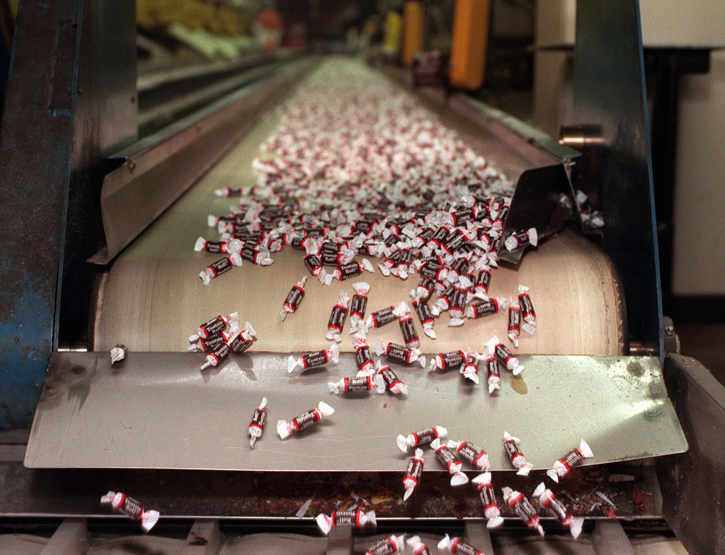 Tootsie Roll candies make their way down a conveyor belt at a plant in Chicago. The Associated Press