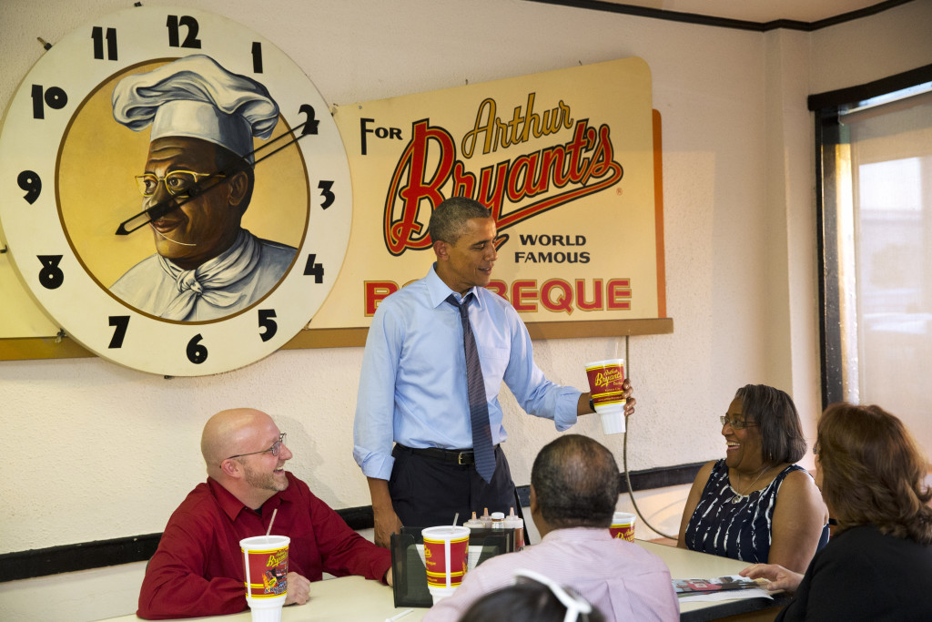 President Barack Obama picks up a souvenir cup while meeting with four Kansas City residents who wrote him letters, over dinner at a restaurant in Kansas City, Mo. Clockwise from left are Victor Fugate, the president, Becky Forrest, Valerie McCaw, and Mark Turner. Fugate is a guest to watch Obama's State of the Union address. The Associated Press