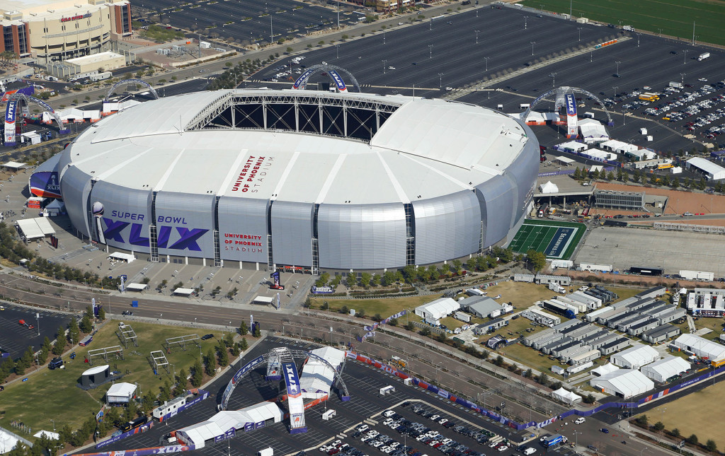 The playing field for the NFL Super Bowl XLIX football game is rolled into the University of Phoenix Stadium Wednesday in Glendale, Ariz.  The Associated Press