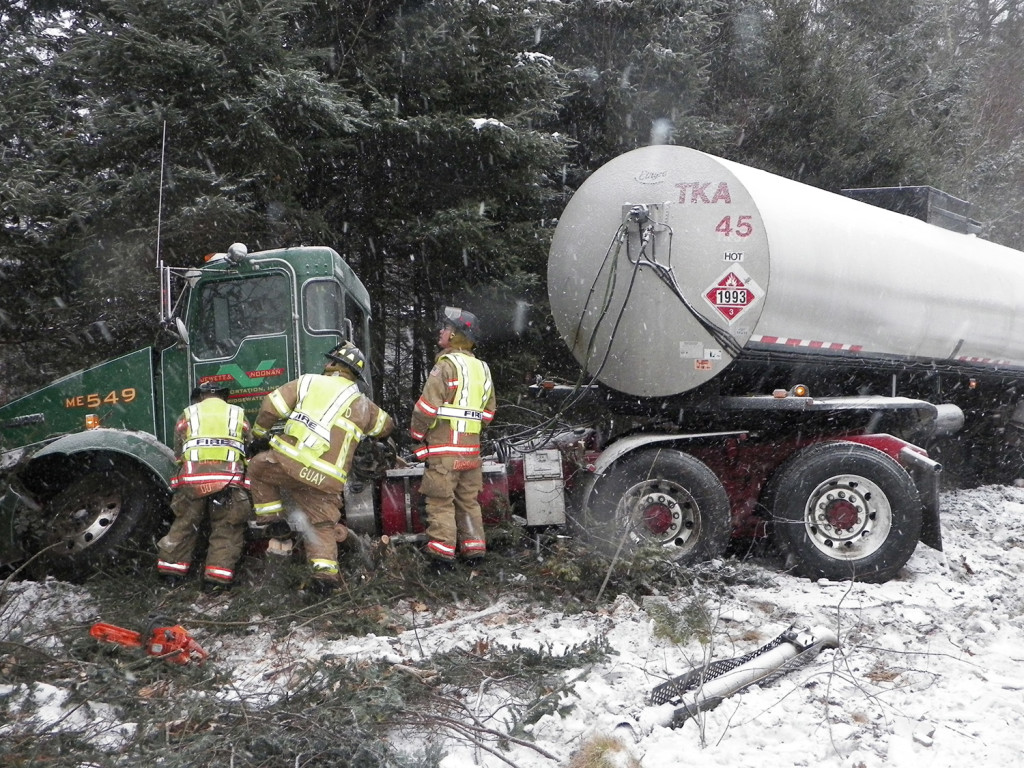 Emergency personnel work on an oil tanker truck Friday after it slid off the Maine Turnpike around mile marker 28 southbound in Arundel.
