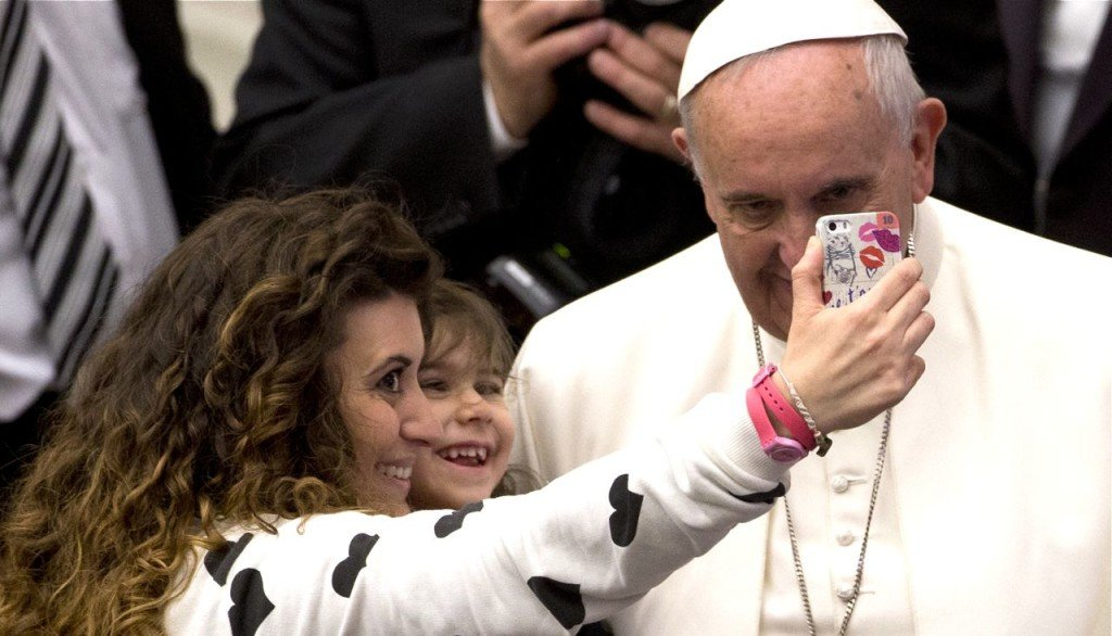 A woman and a child take a selfie photo with Pope Francis  during his weekly general audience in the Paul VI hall at the Vatican, Wednesday. The Associated Press