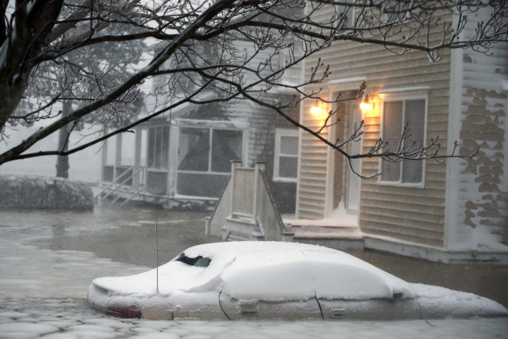 Water floods a street on the coast in Scituate, Mass., Tuesday.
