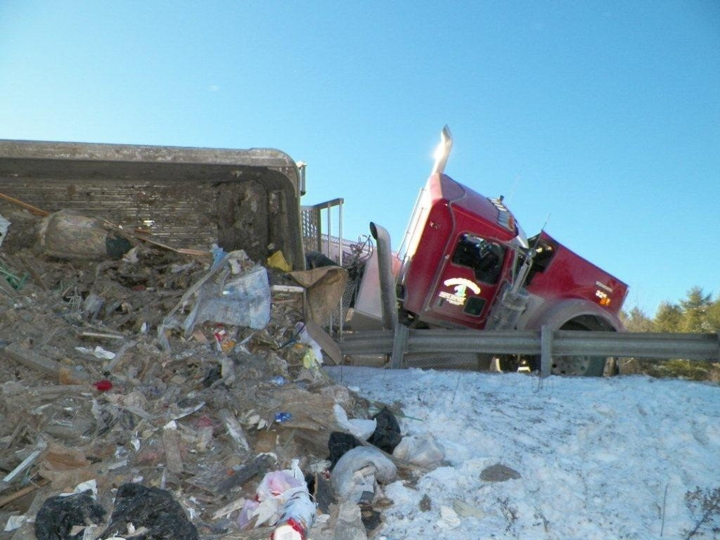 Work continues to remove the wreck of a tractor-trailer garbage truck that overturned along I-95 in Augusta Tuesday.  The northbound lanes remain down to one lane and backups were expected to continue throughout the day. Courtesy Maine Department of Public Safety