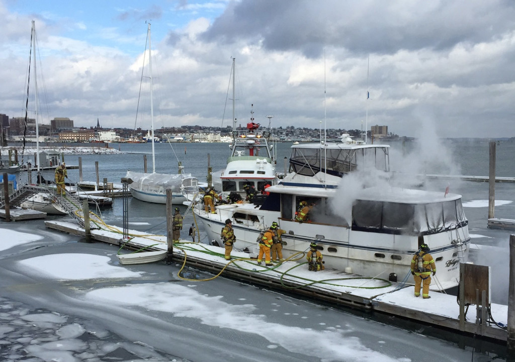 Firefighters work to extinguish a fire aboard a boat at South Port Marine in South Portland on Friday.
