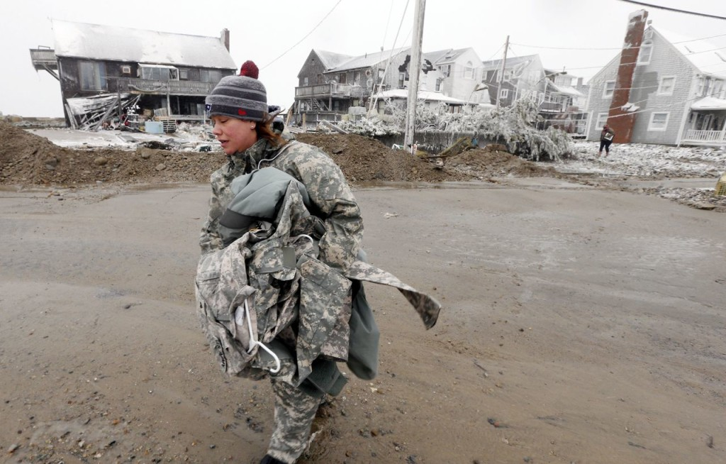 U.S. Army soldier Jennifer Bruno carries some belongings from her house, center rear, that was heavily damaged by a storm surge during the blizzard Tuesday in Marshfield, Mass. The Associated Press