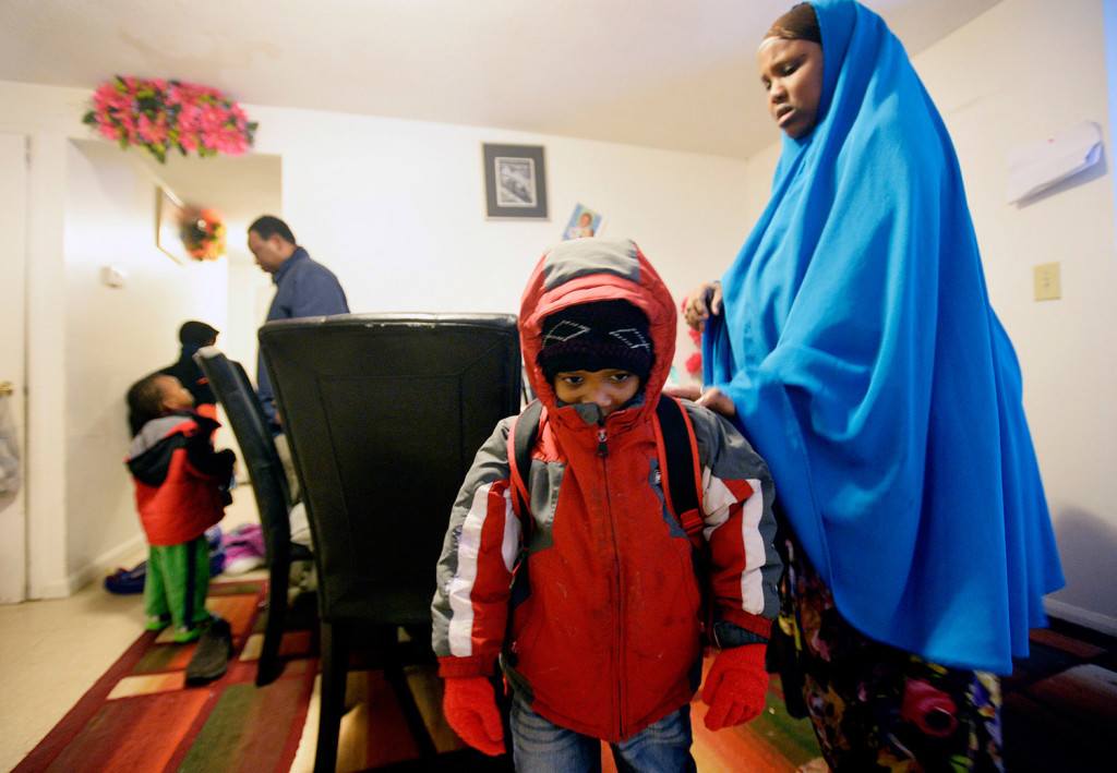 Fadumo Libah helps her son Hudeyfa, 5, put his backpack on as Muhidin Libah, left, helps the other children get ready for school.
