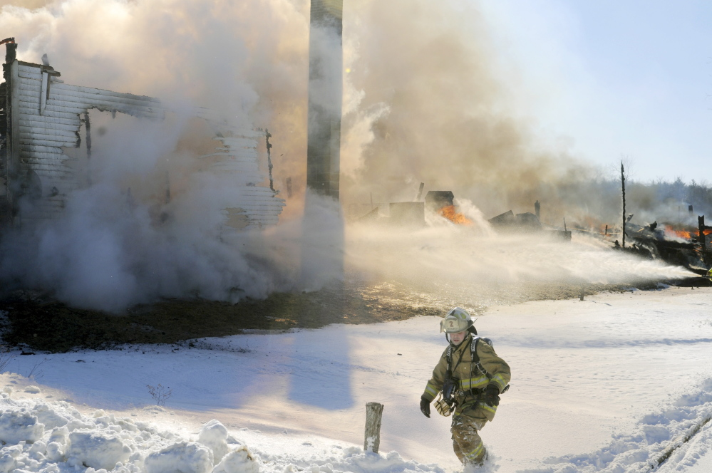 A firefighter climbs through a snowbank as a farmhouse is engulfed in flames on Route 105 in Somerville on Sunday.