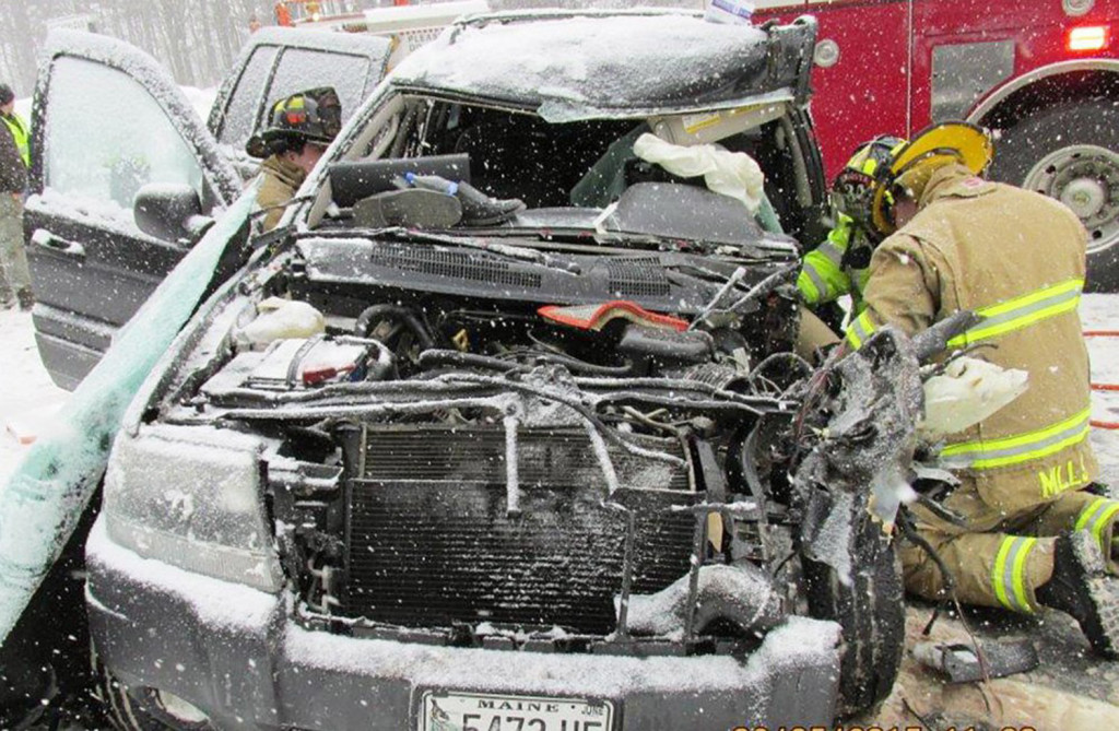 Augusta firefighters extricate victims from a sport utility vehicle that collided with a Department of Transportation snowplow Thursday on Interstate 95 in Augusta.