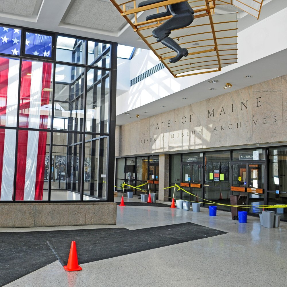 In front of the doors to the state's library, museum and archives, buckets and trash cans catch drips from the leaky ceiling Wednesday in the Maine State Cultural Building's lobby in Augusta.