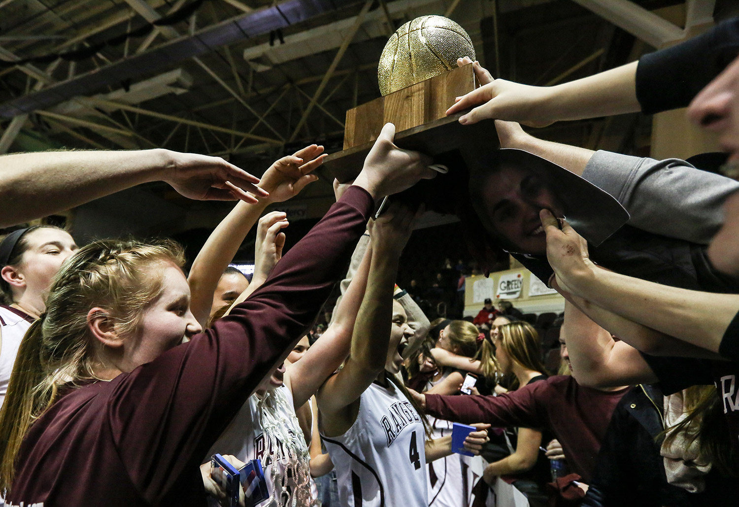 FEB. 27 FINALS: The Greely girls' basketball team passes the Class B state championship trophy into the student section at the Cross Insurance Arena in Portland after beating Presque Isle, 56-39, on Friday night.
