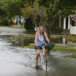 Bicyclists navigate a flooded street after Hurricane Arthur passed through Manteo, a town on North Carolina's Roanoke Island. The state's Outer Banks will see more frequent destructive tidal flooding as sea levels rise over the next 30 years, several studies say.
