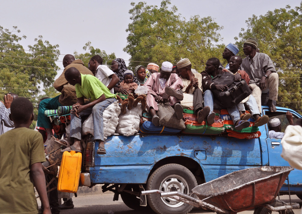 Villagers wait on a small truck as they and others flee recent violence near Maiduguri, Nigeria. The Associated Press
