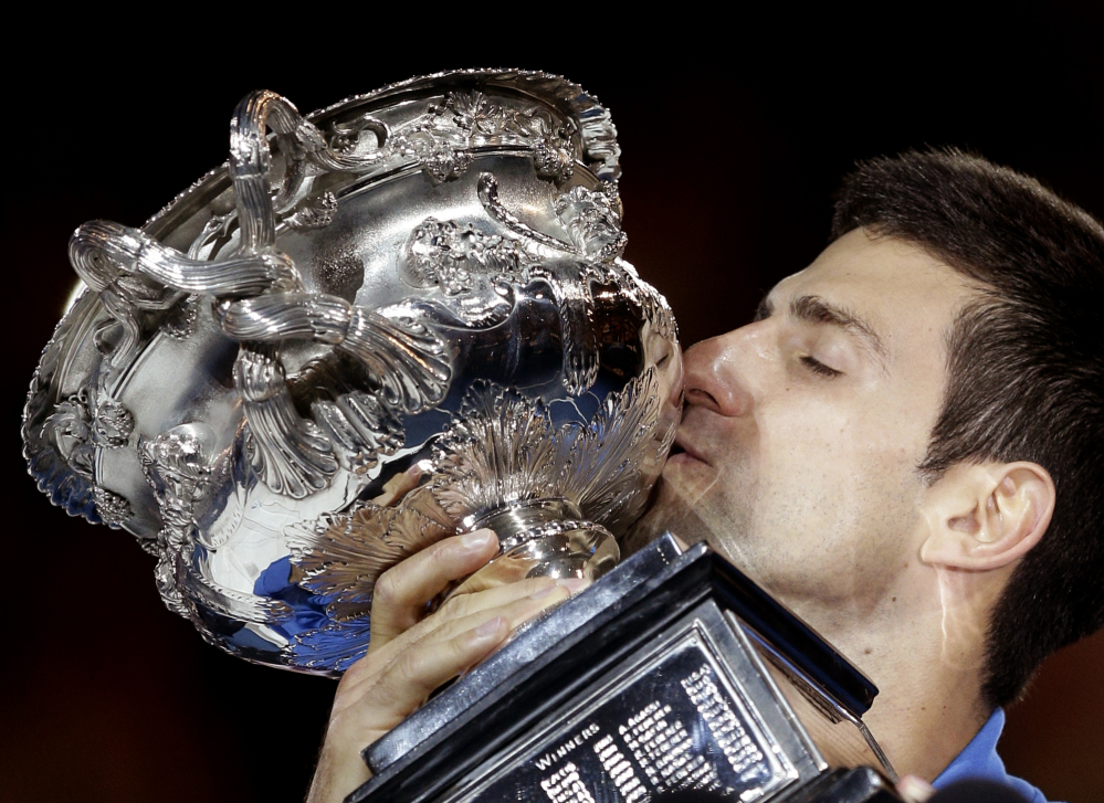 Novak Djokovic kisses the trophy after defeating Andy Murray in during the men's singles final at the Australian Open in Melbourne, Australia, on Sunday.