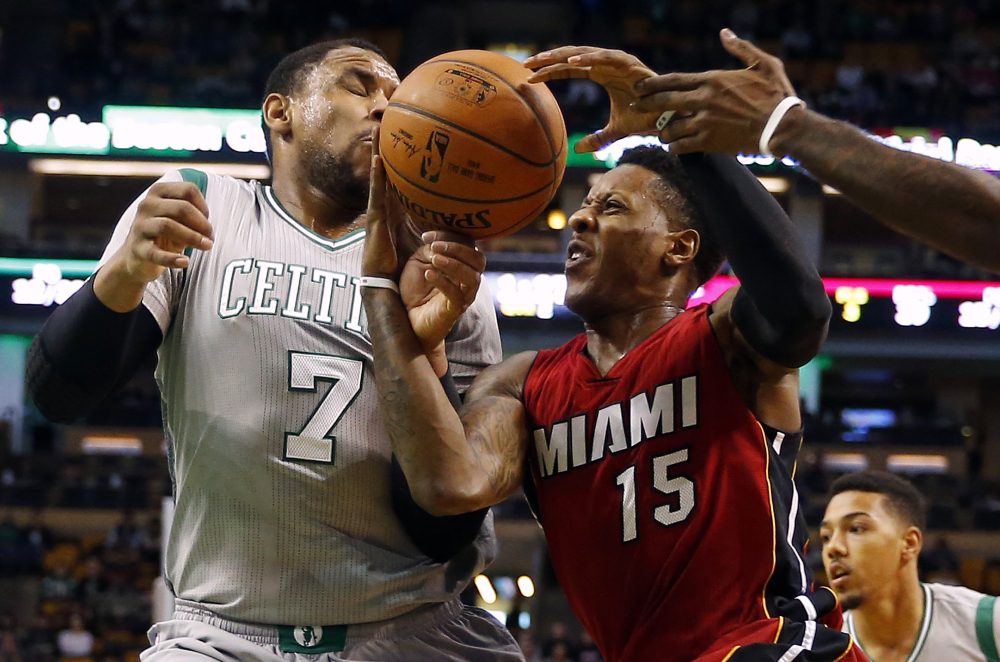 Miami Heat's Mario Chalmers, 15, tries to hold on to the ball while getting by Boston Celtics' Jared Sullinger in the first half Sunday in Boston.