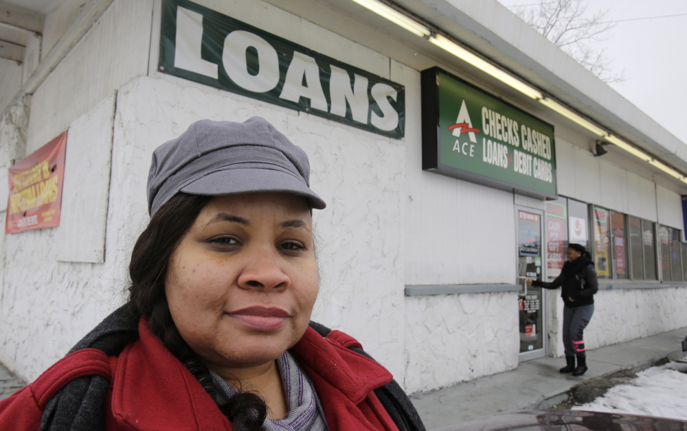 A customer stands outside a payday loan business in Cleveland where she initially borrowed $500 but was forced to keep borrowing to pay back the initial loan. A federal agency is stepping up enforcement to prevent cycles of high-rate debt.