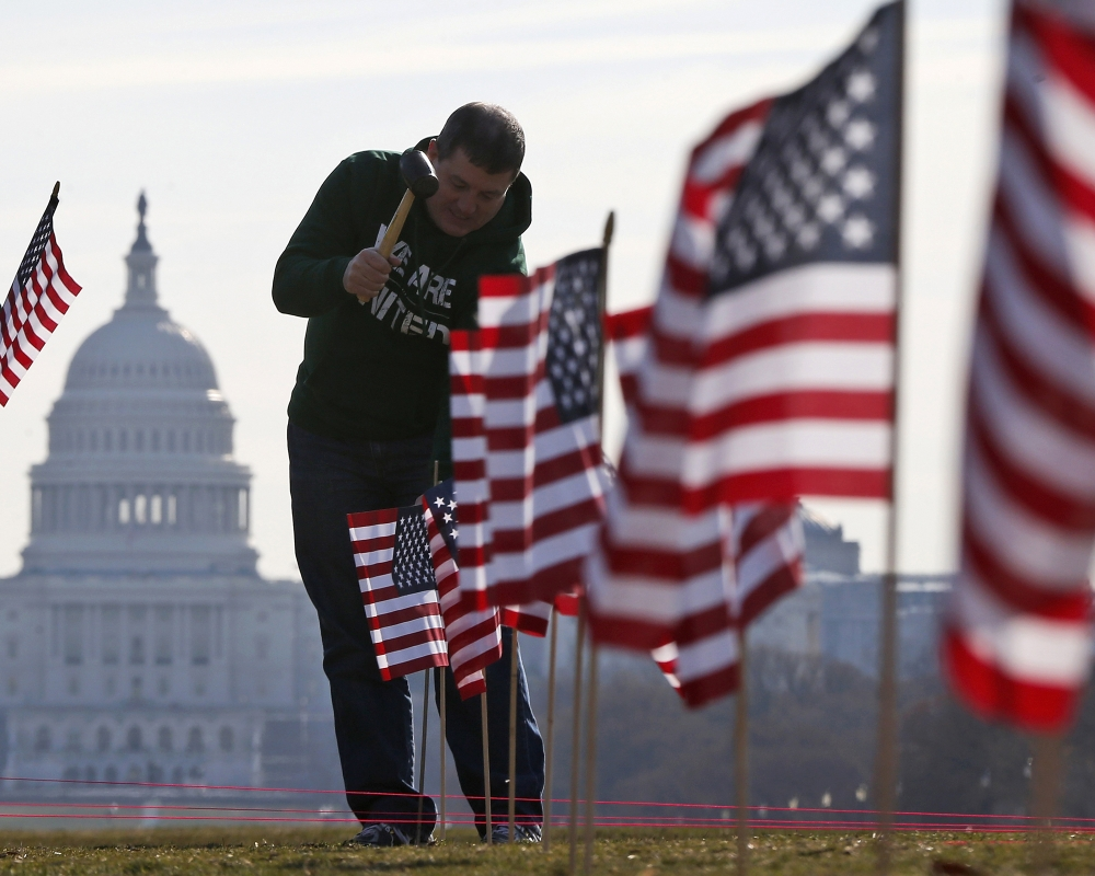 With the Capitol in the background, flags representing veterans and service members who died by suicide in 2014 are placed on the National Mall in Washington.