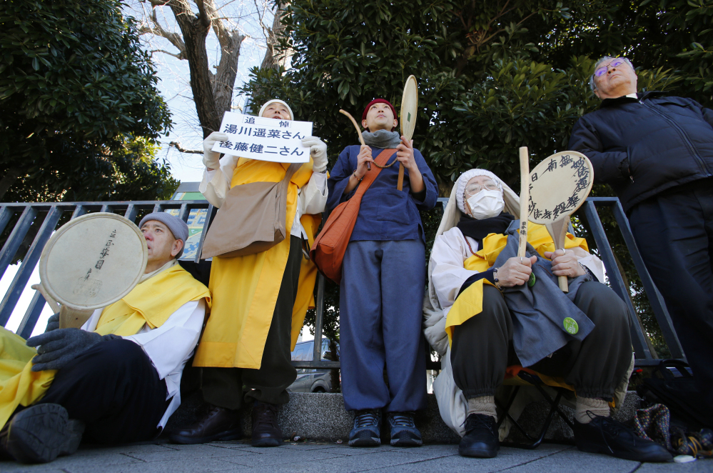 Buddhist monks chant a mantra while beating drums in memory of two Japanese hostages, Kenji Goto and Haruna Yukawa, killed by the Islamic State group, in front of the prime minister's residence in Tokyo on Monday.