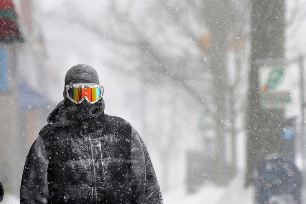 Guy Cournoyer of Northampton adds some color to an otherwise whiteout day in downtown Northampton, Mass., on Monday. Cournoyer says the combination of ski goggles and a full head-covering balaclava leaves no exposed skin.