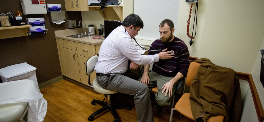 Dr. Brad Huot, a primary care physician at Martin's Point Health Care, checks the heart rate of patient Tyson O'Keefe of Portland. A hybrid form of Medicaid expansion would help more Mainers access care.