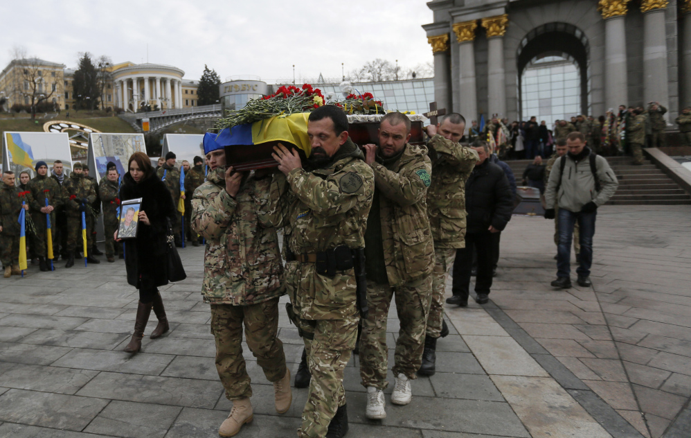 Ukrainian soldiers carry a coffin in Kiev, Ukraine, bearing the body of a serviceman who was killed in fighting against Russian-backed separatists. Ukraine officials say five soldiers were killed and 29 wounded in fighting Monday.