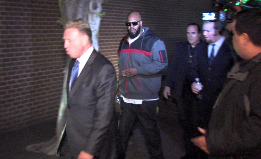 "Death Row Records founder Marion ""Suge"" Knight, right, walks into the Los Angeles County Sheriff's Department early Friday morning in connection with a hit-and-run that killed one man and another injured. Knight was charged Monday with murder and attempted murder."