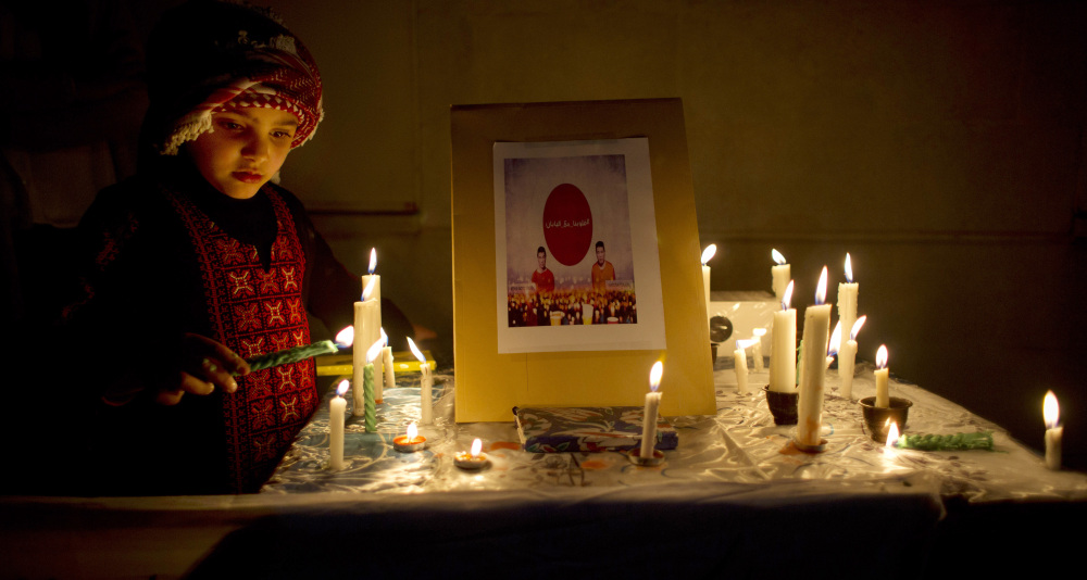 A Jordanian child lights a candle by a picture of two slain Japanese hostages Haruna Yukawa, right and Kenji Goto during a candle vigil in support of Japan, in front of the Japanese embassy, in Amman on Monday,