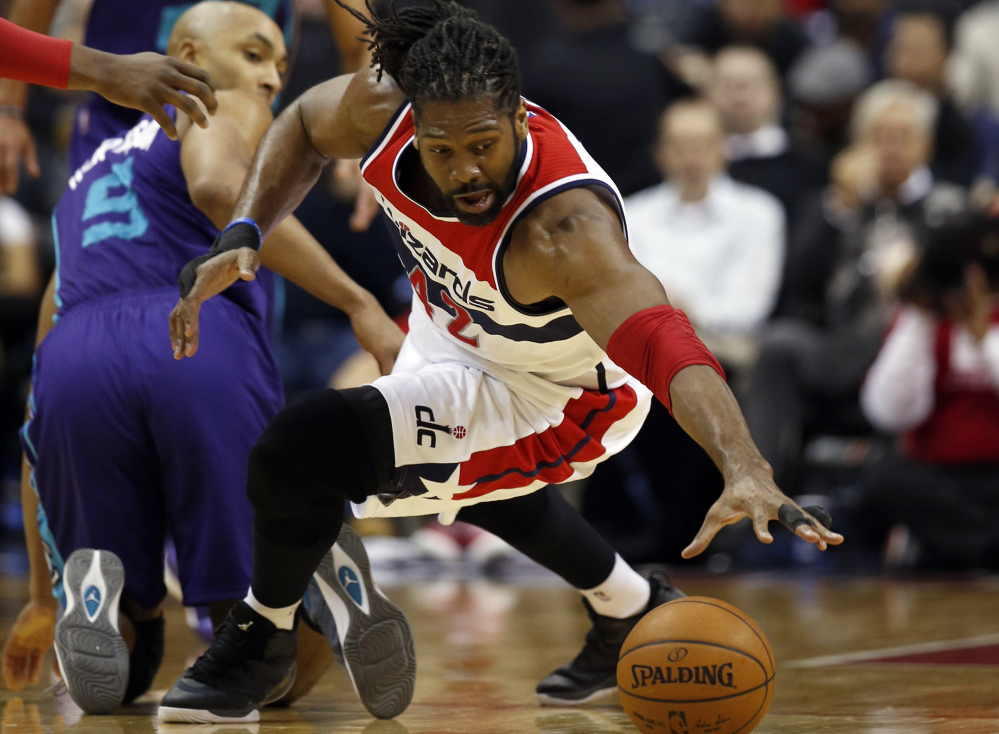 Washington forward Nene dives to get control of a loose ball in front of Charlotte's Jannero Pargo during the Hornets' 92-88 win Monday night in Washington.