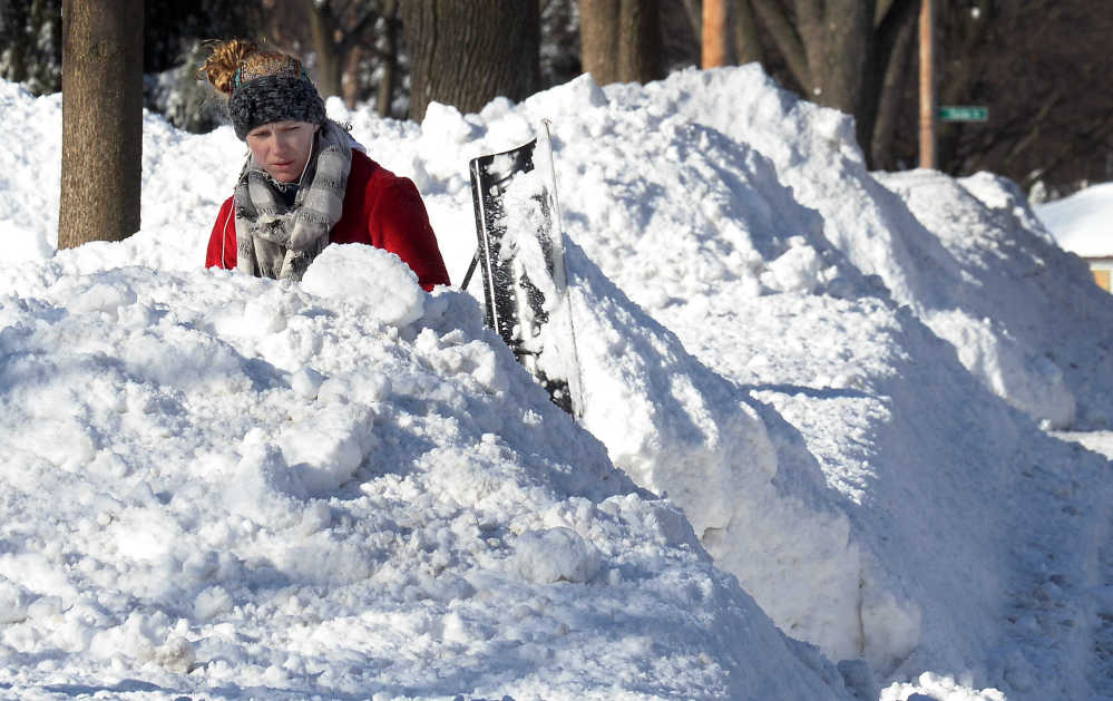 Lauren Rosengarden of Mount Prospect, Ill. digs out her driveway on Monday the day after a significant snowfall. The Associated Press