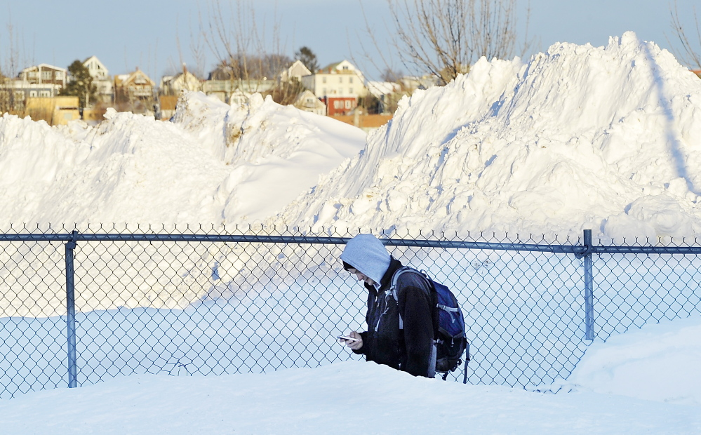 Amid piles of snow, Andrew Bove trudges home from work at the Preble Street Resource Center. It could be worse: Eastport got 76 inches in a week.