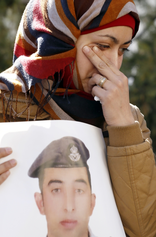 Anwar al-Tarawneh, the wife of Jordanian pilot Lt. Muath al-Kaseasbeh, who was killed by Islamic State group militants, holds a poster of him as she weeps during a protest in Amman, Jordan, on Tuesday.