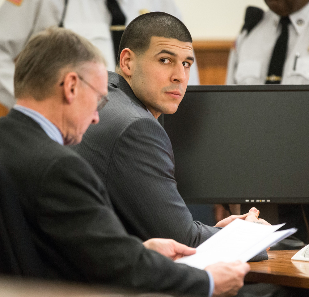 Former New England Patriots player Aaron Hernandez, right, glances towards the Lloyd family during his trial at Bristol County Superior Court in Fall River, Mass.