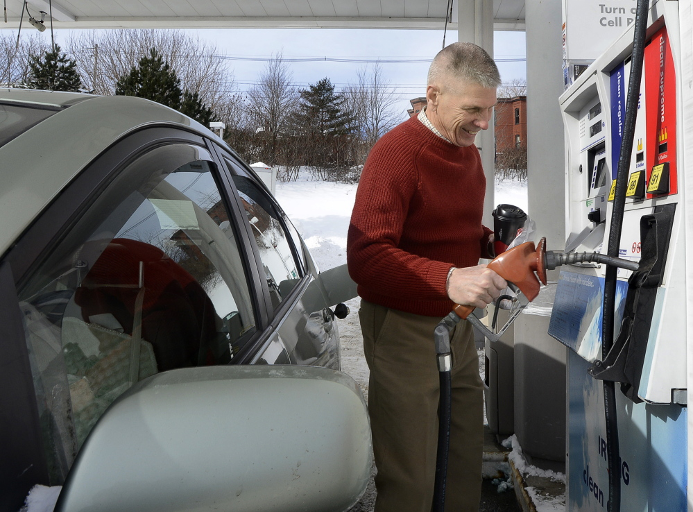 """Sam Davidson of Portland fuels up Tuesday at the Irving station on Commercial Street in Portland. He said his Prius gets 53 mpg, but he's still """"delighted"""" with the low prices."""