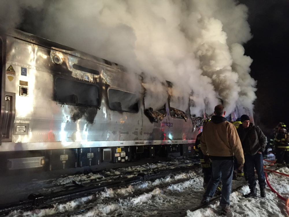 The Metro-North Railroad passenger train smolders after hitting a sport utility vehicle Tuesday evening in Valhalla, N.Y.